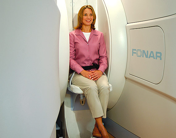 An image showing how a patient seated during a spinal scan in an open MRI scanner to show the extra pressure